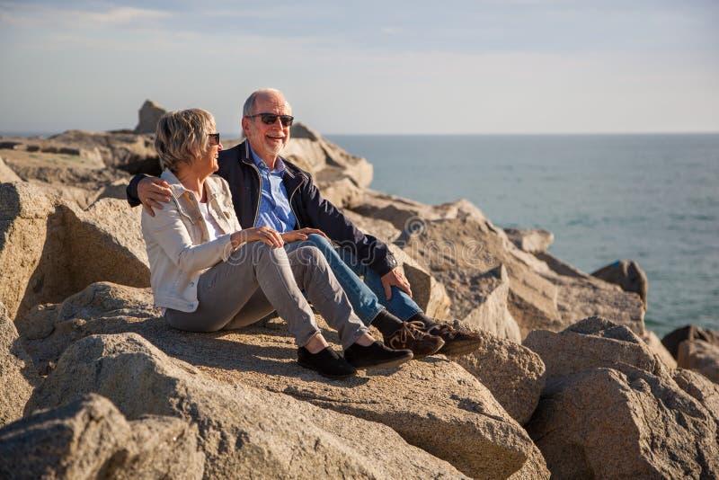 Pares mayores felices que se sientan en rocas por el mar fotografía de archivo libre de regalías
