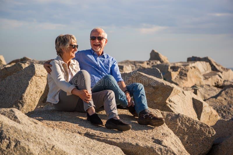 Pares mayores felices que se sientan en rocas por el mar imagen de archivo libre de regalías
