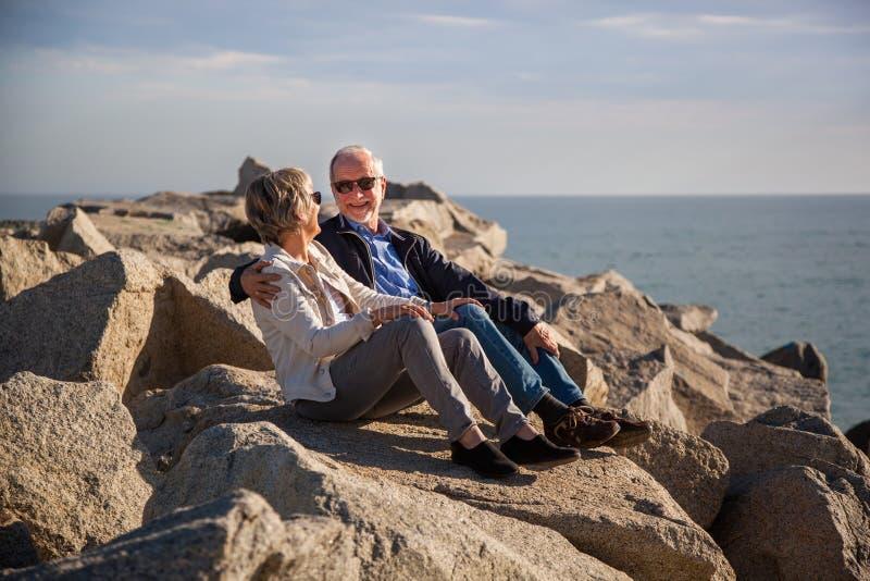 Pares mayores felices que se sientan en rocas por el mar fotos de archivo