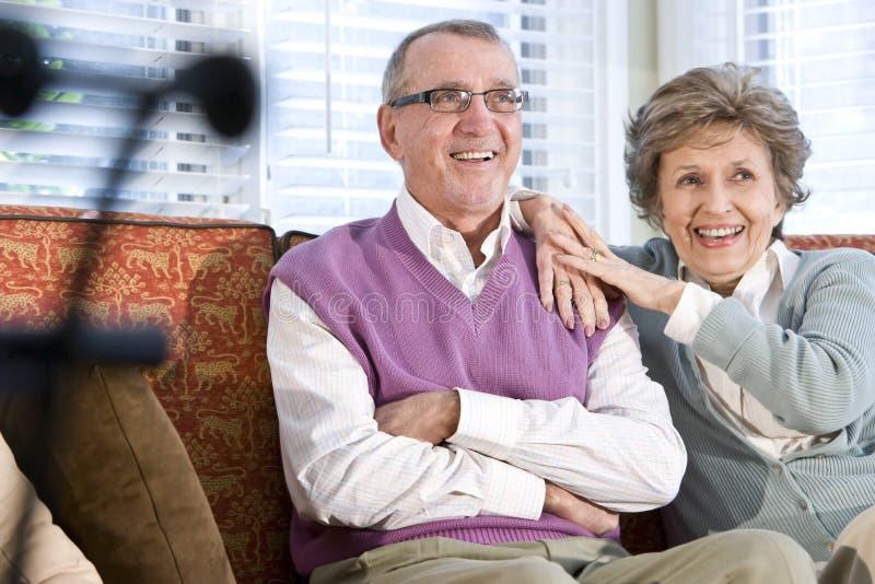 Pares mayores felices que se sientan junto en el sofá imagen de archivo libre de regalías