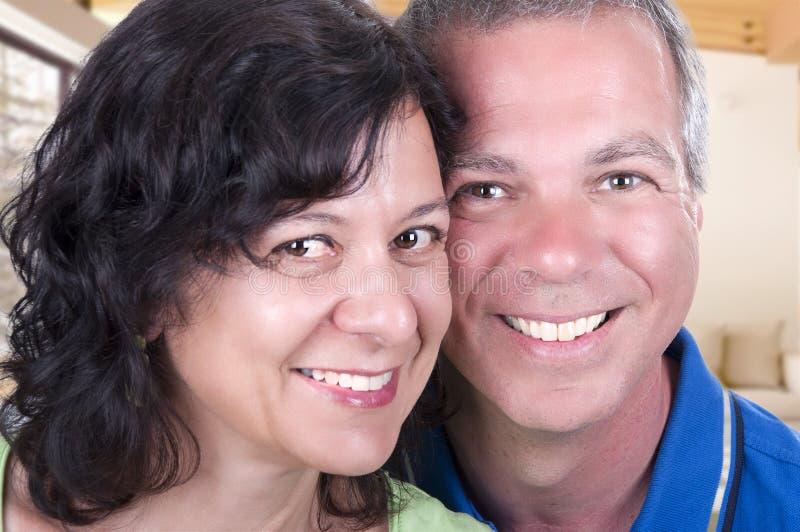 Pares mayores felices que sonríen en casa foto de archivo