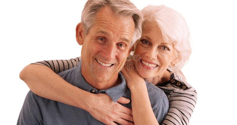 Pares mayores felices que sonríen en la cámara en el fondo blanco imagen de archivo