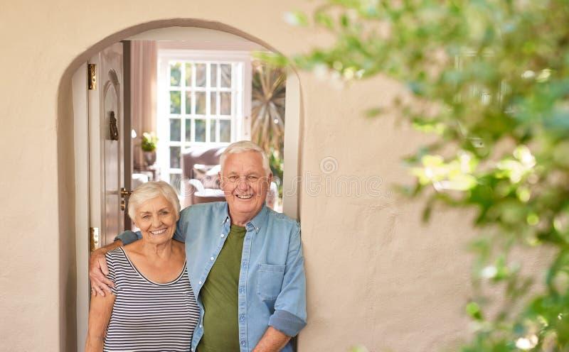 Pares mayores felices que sonríen welcomingly en su puerta principal foto de archivo libre de regalías
