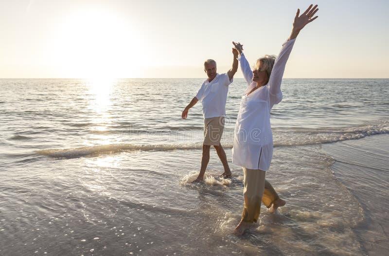 Pares mayores felices que sostienen la playa de la salida del sol de la puesta del sol de las manos imagen de archivo