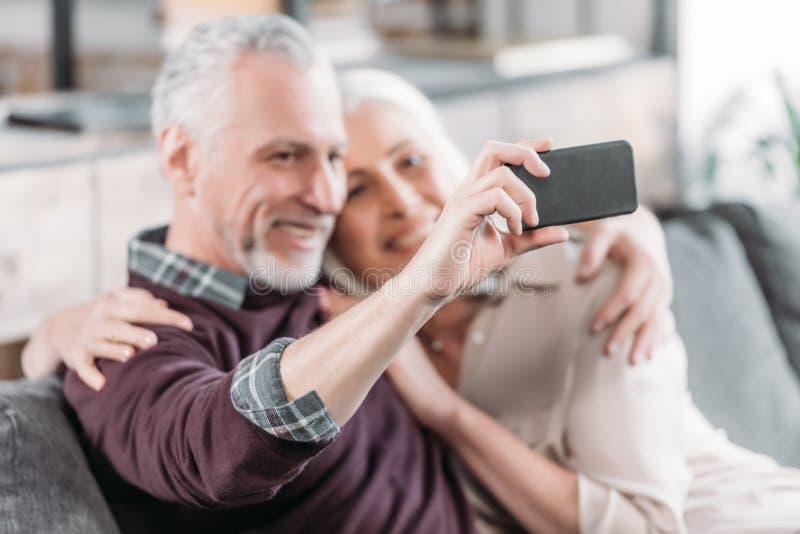 Pares mayores felices que toman el selfie mientras que descansa sobre el sofá en casa imagen de archivo libre de regalías