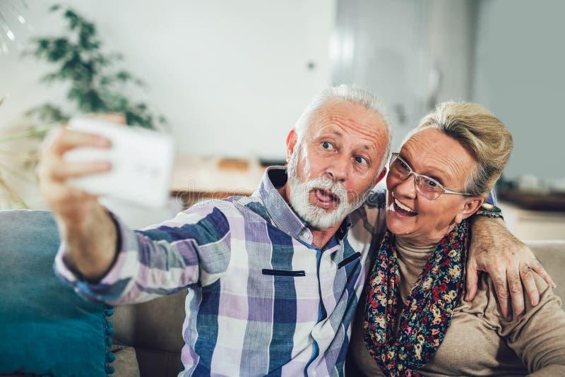 Pares mayores felices que toman un selfie con un teléfono fotos de archivo libres de regalías