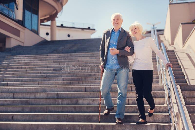Pares mayores felices que van abajo de las escaleras fotografía de archivo
