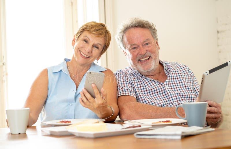 Pares mayores felices usando el teléfono y la tableta elegantes mientras que desayunando imágenes de archivo libres de regalías