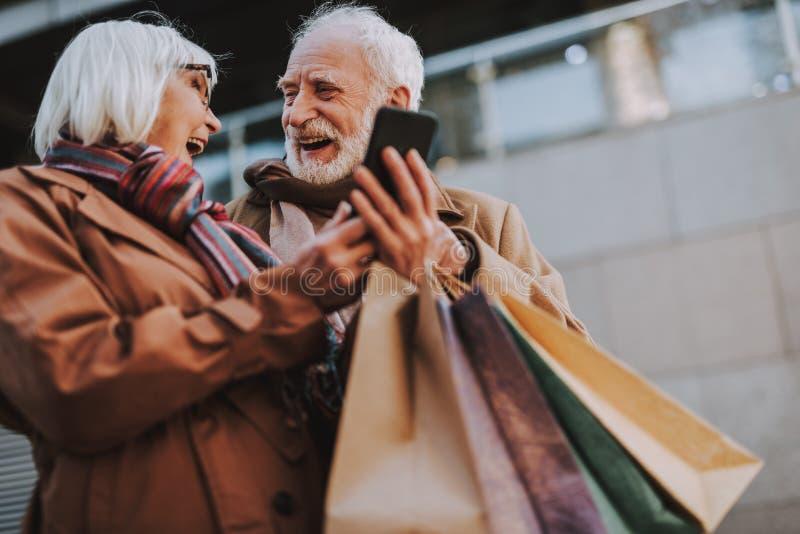 Pares mayores felices usando smartphone en la calle imagenes de archivo