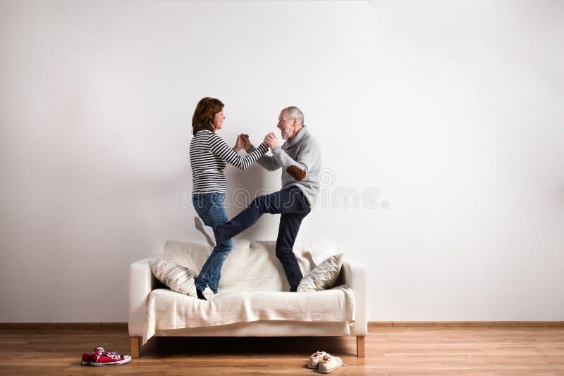 Pares mayores hermosos que se colocan en el sofá, bailando Tiro del estudio imagen de archivo libre de regalías