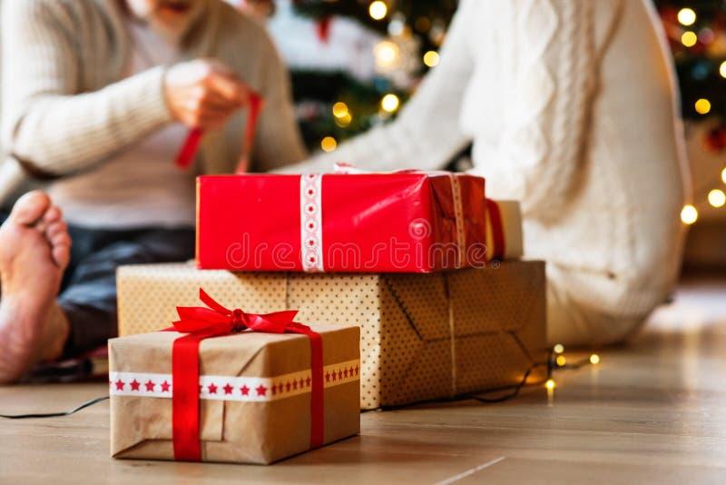 Pares mayores irreconocibles delante del árbol de navidad con pre fotos de archivo