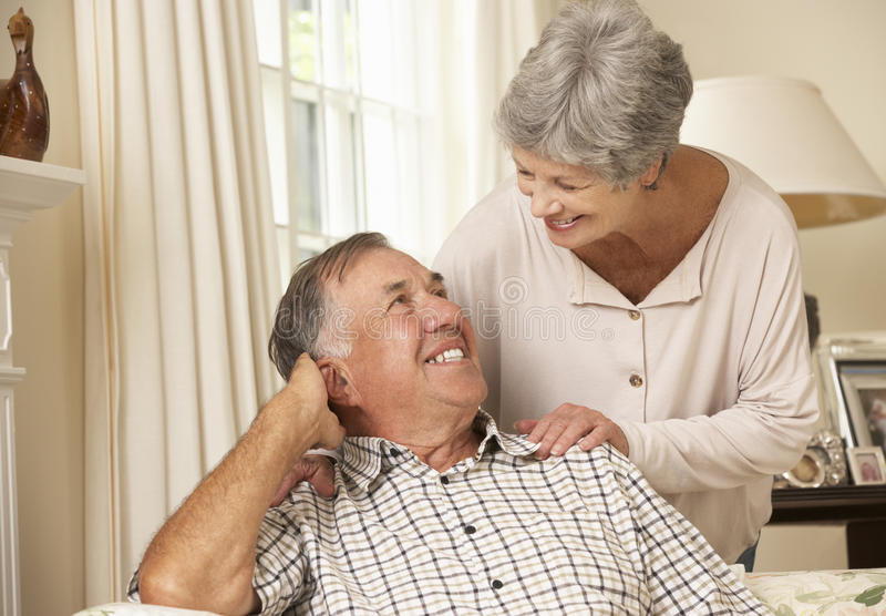 Pares mayores jubilados que se sientan en Sofa At Home Together imágenes de archivo libres de regalías