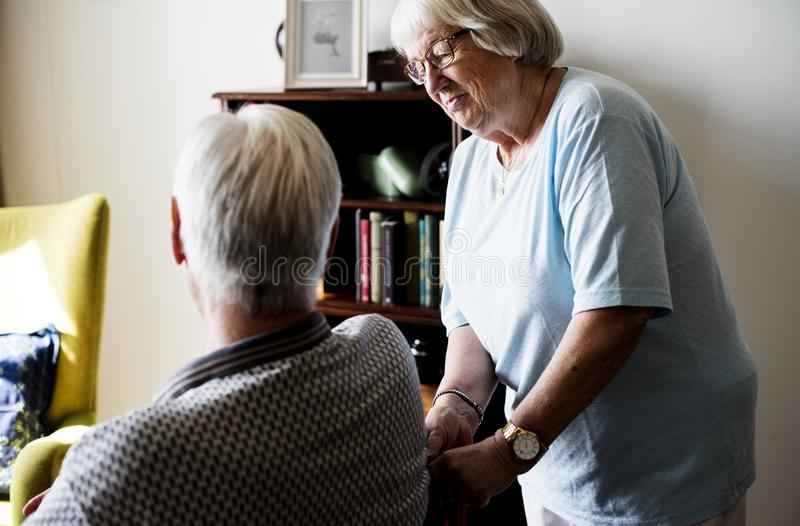 Pares mayores, mujer mayor que toma cuidado de un hombre mayor imagen de archivo
