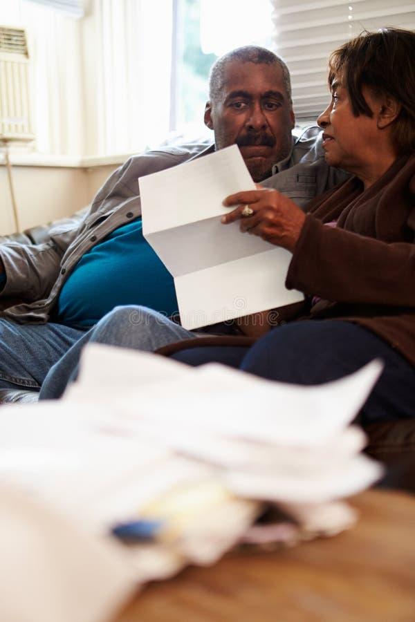 Pares mayores preocupantes que se sientan en Sofa Looking At Bills fotografía de archivo
