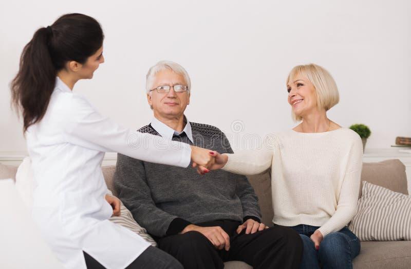Pares mayores que acogen con satisfacción al doctor durante la visita casera imágenes de archivo libres de regalías