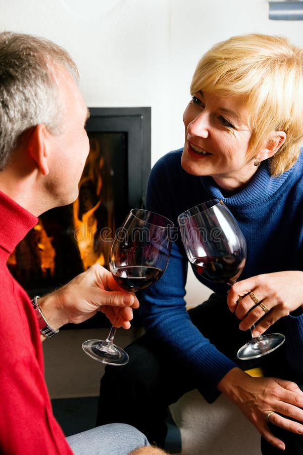 Pares mayores que beben el vino rojo imagenes de archivo