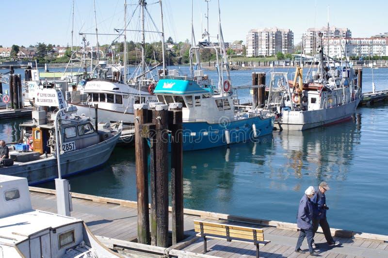 Pares mayores que caminan en barcos de pesca fotos de archivo