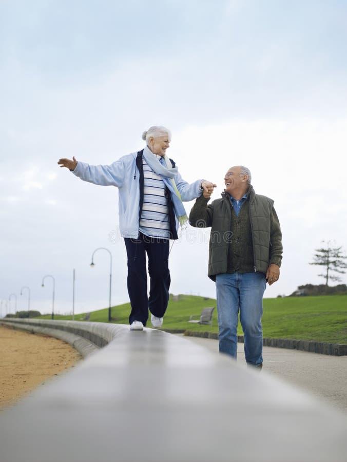 Pares mayores que caminan en la pared que lleva a cabo las manos fotografía de archivo libre de regalías