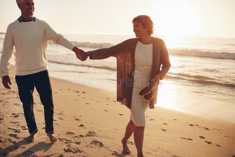 Pares mayores que caminan en la playa junto en la puesta del sol fotografía de archivo libre de regalías
