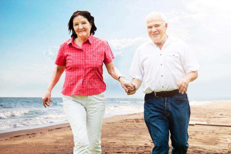 Pares mayores que caminan en la playa imagen de archivo