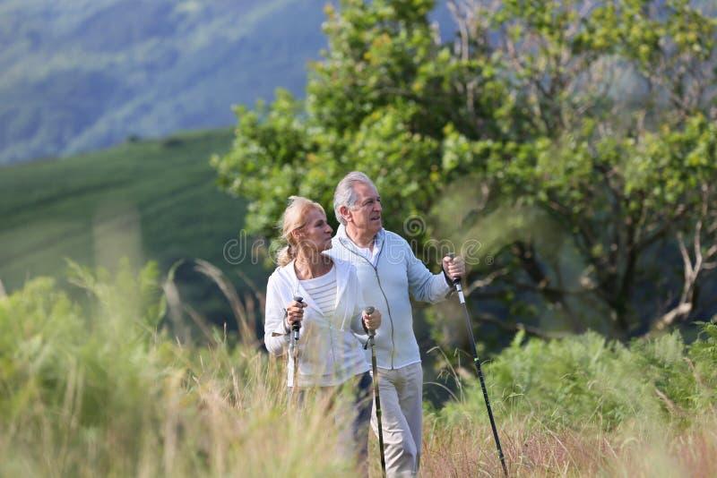 Pares mayores que caminan en paisaje hermoso fotos de archivo libres de regalías
