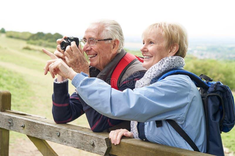 Pares mayores que caminan en puerta que hace una pausa del campo y que toman la foto con la cámara foto de archivo