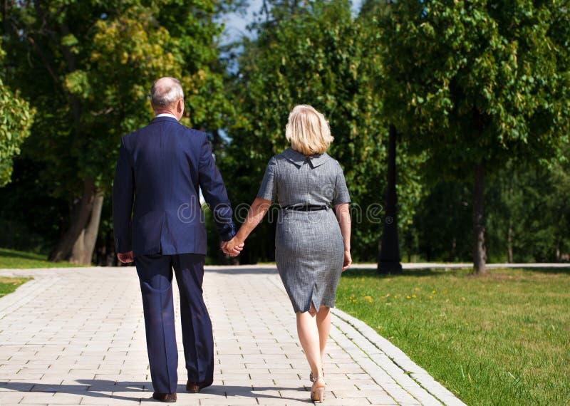 Pares mayores que caminan en verano en parque fotografía de archivo libre de regalías