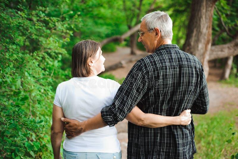 Pares mayores que caminan junto en un bosque, primer fotos de archivo