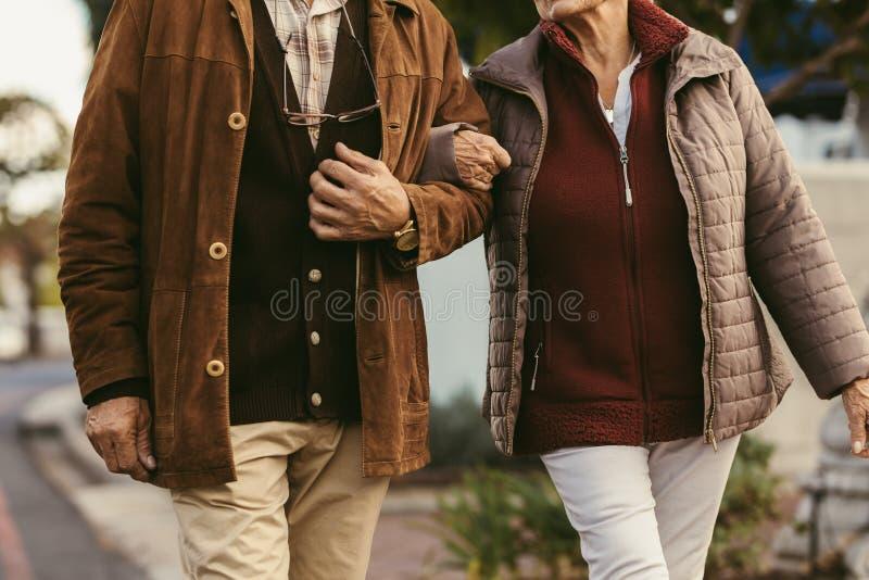 Pares mayores que caminan llevando a cabo las manos foto de archivo libre de regalías