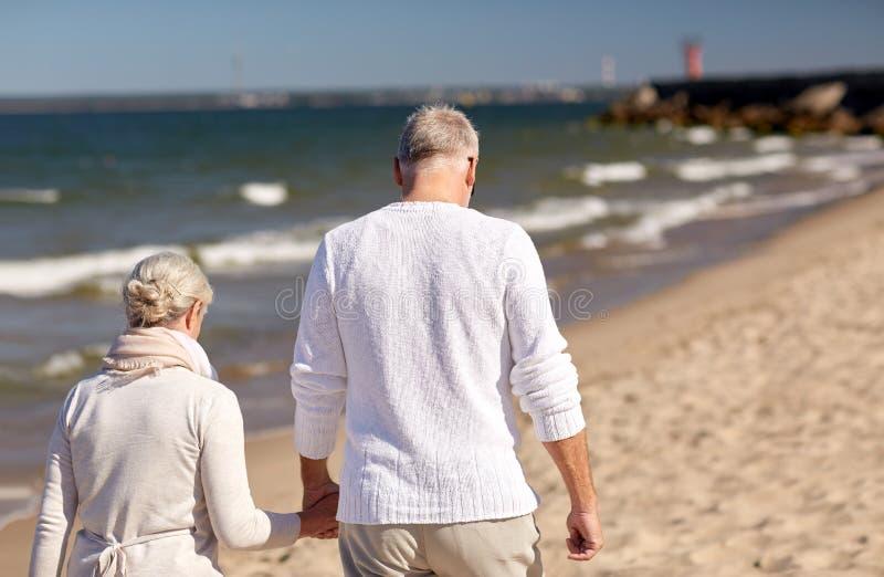 Pares mayores que caminan a lo largo de la playa del verano imagenes de archivo