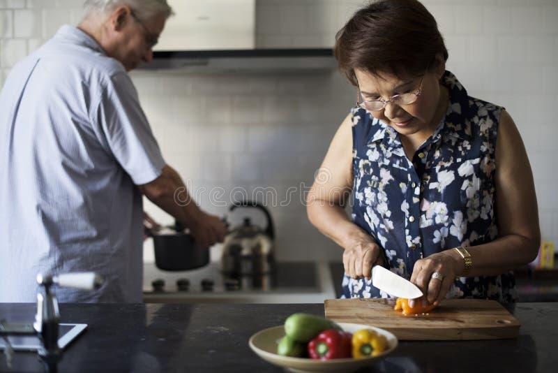 Pares mayores que cocinan la cocina de la comida foto de archivo