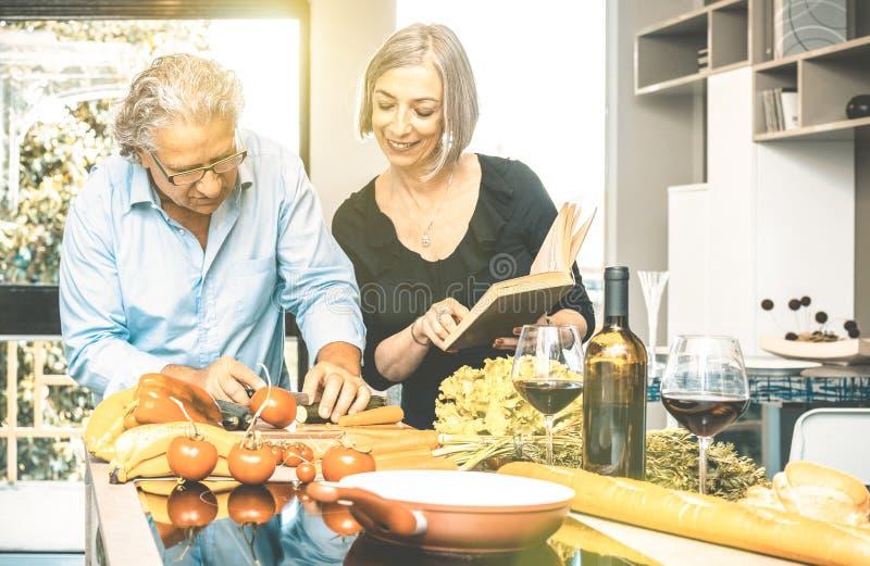 Pares mayores que cocinan la comida sana y que beben el vino rojo imagen de archivo