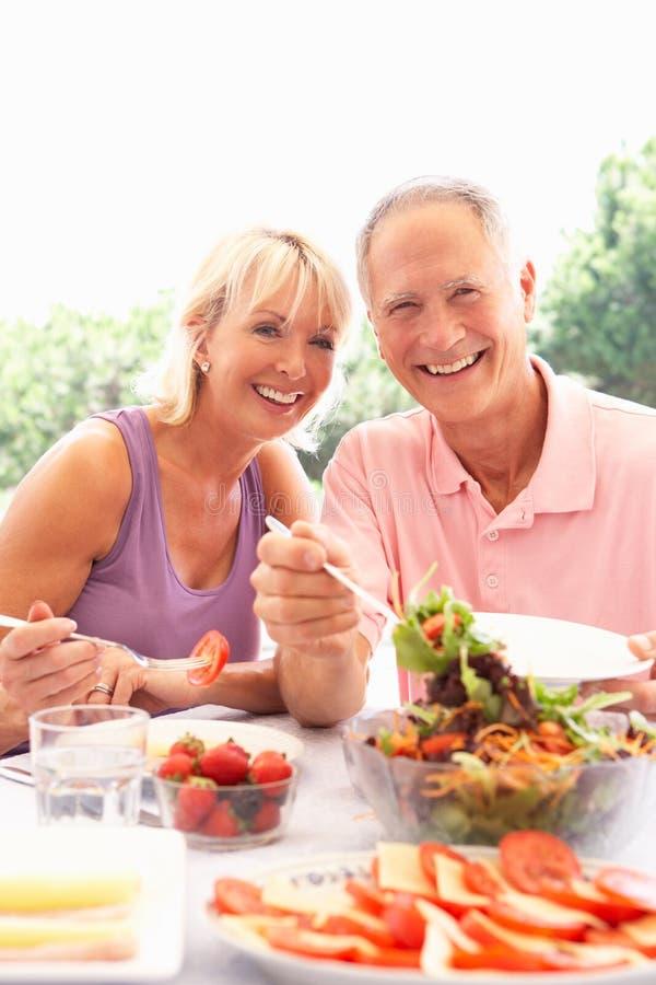 Pares mayores que comen al aire libre imagen de archivo libre de regalías