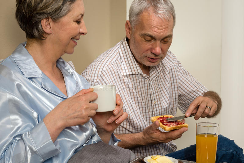 Pares mayores que comen el desayuno romántico en cama fotos de archivo