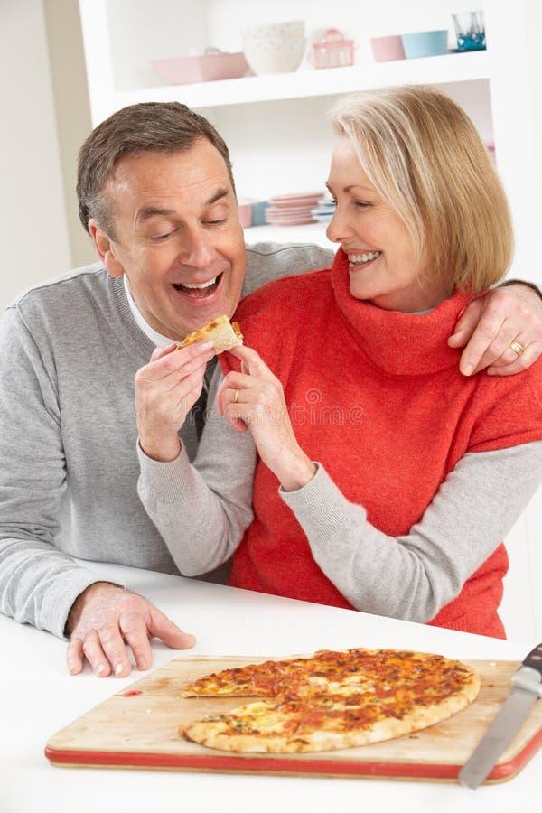 Pares mayores que comparten la pizza para llevar en cocina fotos de archivo