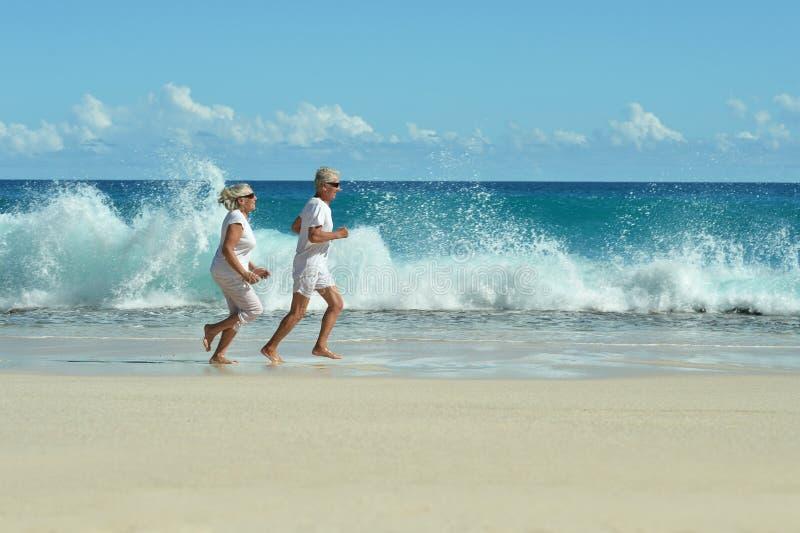Pares mayores que corren en la playa foto de archivo libre de regalías