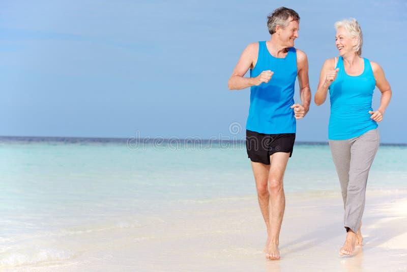 Pares mayores que corren en la playa hermosa imagen de archivo libre de regalías