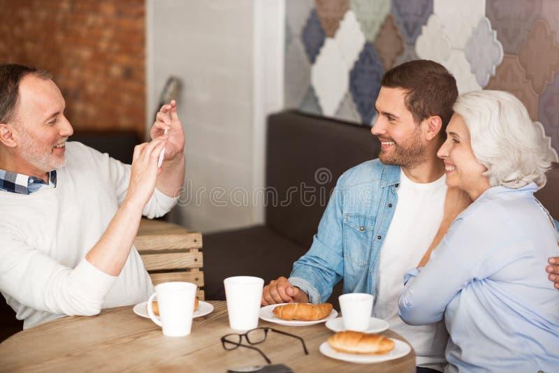 Pares mayores que descansan en el café con su nieto adulto foto de archivo libre de regalías