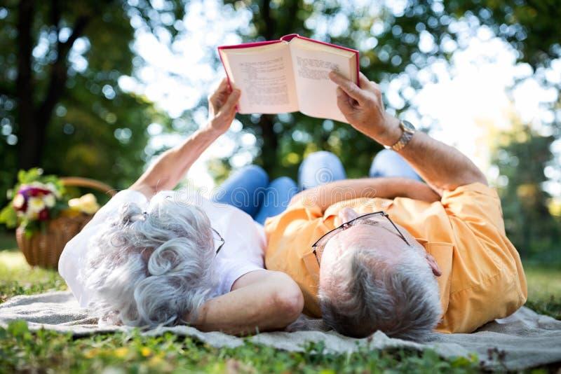 Pares mayores que descansan en el parque, leyendo un libro imágenes de archivo libres de regalías