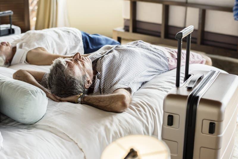 Pares mayores que descansan sobre una cama fotografía de archivo libre de regalías