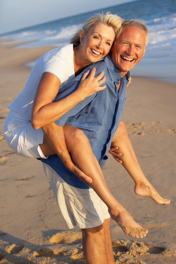 Pares mayores que disfrutan de día de fiesta de la playa fotos de archivo libres de regalías