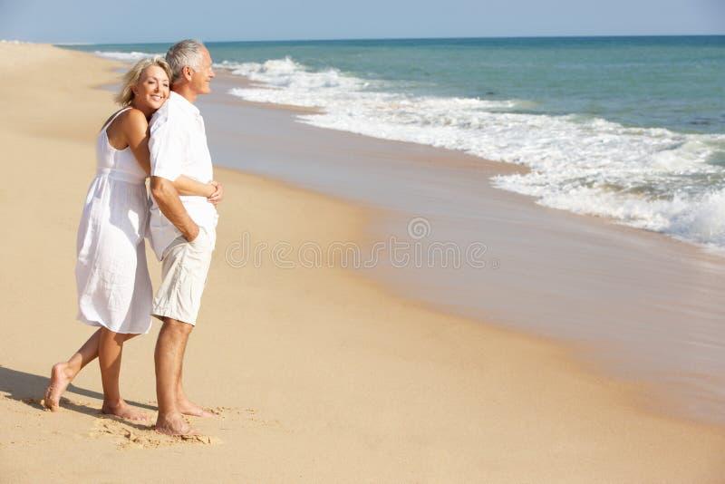 Pares mayores que disfrutan de día de fiesta de la playa en el sol fotos de archivo libres de regalías