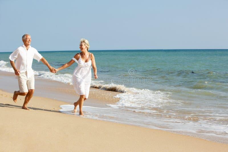 Pares mayores que disfrutan de día de fiesta de la playa en The Sun fotografía de archivo libre de regalías