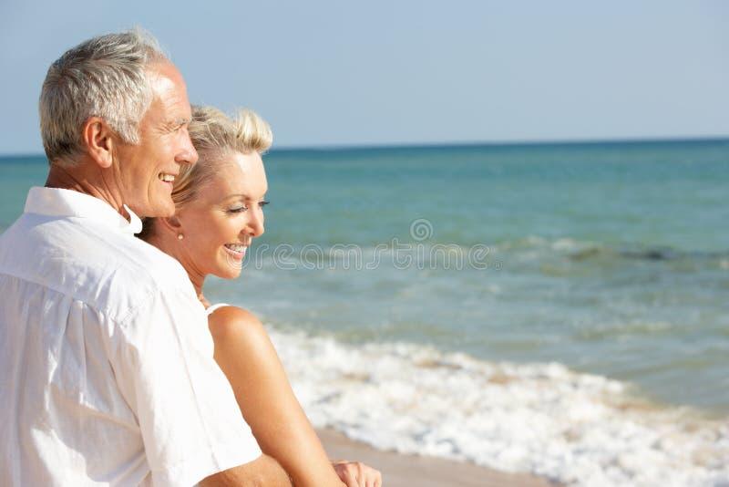 Pares mayores que disfrutan de día de fiesta de la playa en The Sun imagenes de archivo