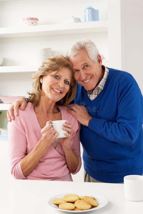 Pares mayores que disfrutan de la bebida caliente en cocina imagen de archivo libre de regalías