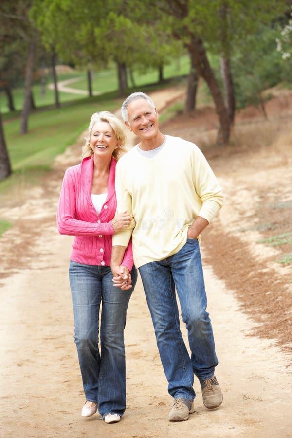 Pares mayores que disfrutan de la caminata en parque imagen de archivo libre de regalías
