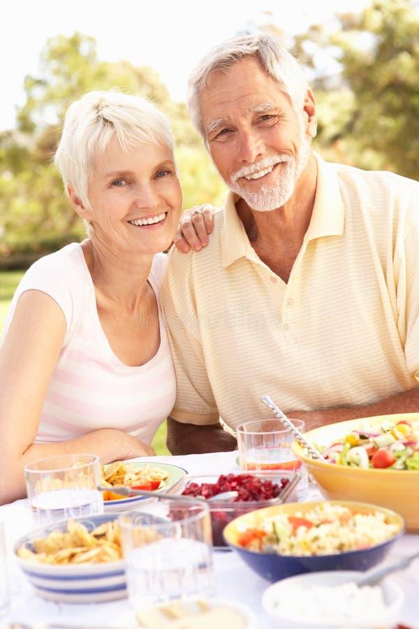 Pares mayores que disfrutan de la comida en jardín foto de archivo