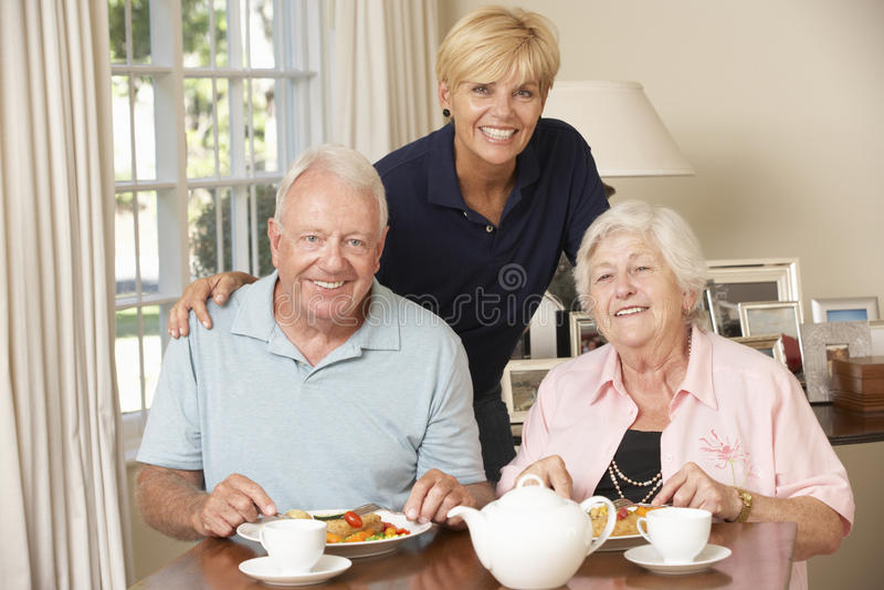 Pares mayores que disfrutan de la comida junto en casa con ayuda a domicilio imágenes de archivo libres de regalías
