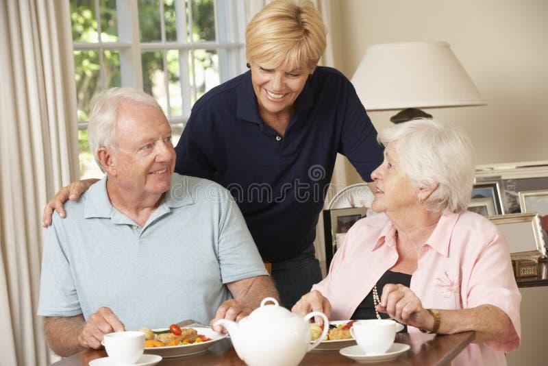 Pares mayores que disfrutan de la comida junto en casa con ayuda a domicilio fotografía de archivo