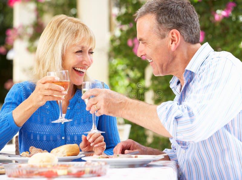 Pares mayores que disfrutan de outdoorss de la comida imagen de archivo